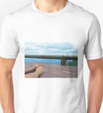 Man hands on a wooden table outside, with cloudy sky. T-Shirt