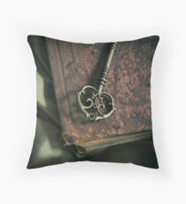 Brass ornamented key on old brown book Throw Pillow
