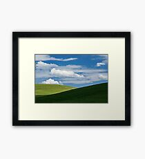 White clouds above green hills Framed Print