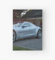 2012 Fisker Karma electric supercar against a sunset Hardcover Journal
