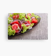 Side view on a diagonal on a plate with fresh salad of raw vegetables closeup Canvas Print