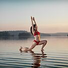 Woman doing Hatha yoga Anjaneyasana Low Lunge pose on the water art photo print by ArtNudePhotos