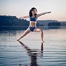 Young woman in blue swimsuit practicing yoga on the water Veerabhadrasana pose art photo print by ArtNudePhotos