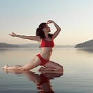 Woman practicing yoga on platform in the water doing Pigeon pose variation art photo print by ArtNudePhotos