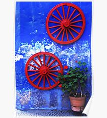 Geranium and red wheels on the blue wall Poster