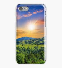 village on hillside meadow with forest in mountain at sunset iPhone Case/Skin