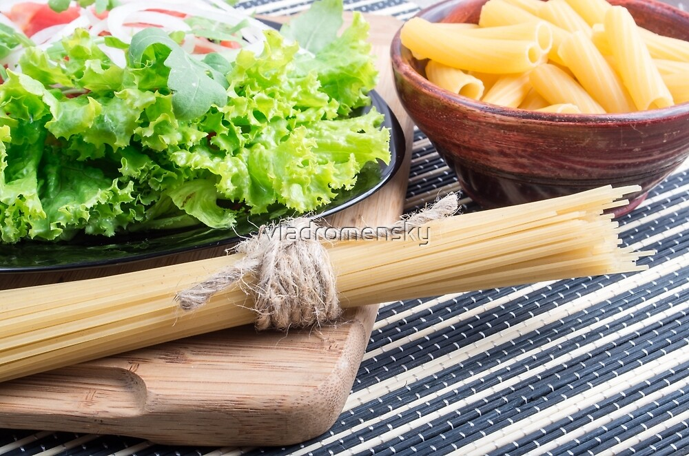 View close-up on uncooked pasta and spaghetti with green salad by vladromensky