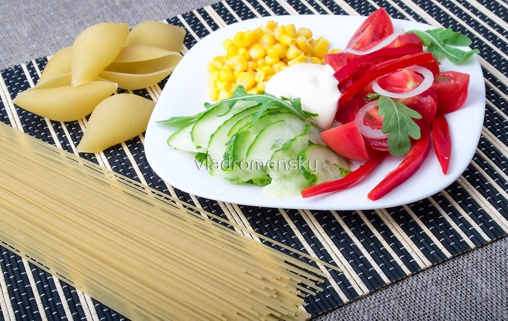 Pieces of fresh raw vegetables on a white plate by vladromensky