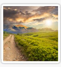 gravel road to high mountains at sunset Sticker