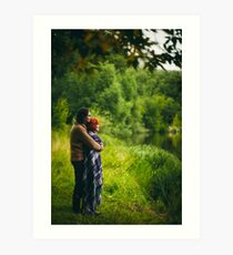 Young happy couple standing near water in green forest Art Print