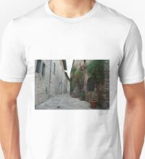 Street in Assisi with stone buildings and flowers T-Shirt