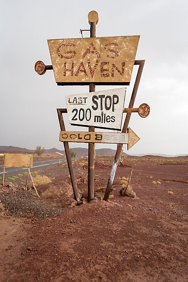 Tall vintage gas sign standing in the desert by Piccaya