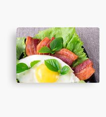 Yolk, fried bacon, herbs and lettuce close-up Canvas Print