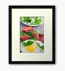 Yolk, fried bacon, herbs and lettuce close-up Framed Print
