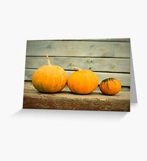 Pumpkins on a wooden background Greeting Card