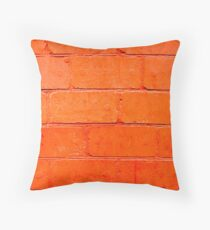 Red background of bricks with a layer of paint close-up Throw Pillow