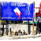 Women sitting under the billboards in Aleppo by Giuseppe Cocco