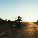 Silhouette of Boy Riding Bicycle at Sunset in Burmese Countryside by visualspectrum