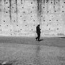 Man Walking Past Ancient City Wall by visualspectrum