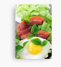 Plate with egg yolk, fried bacon and herbs Canvas Print