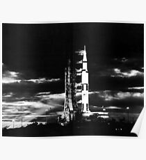 Searchlights illuminate this nighttime view of Apollo 17 spacecraft on its launchpad. Poster