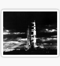 Searchlights illuminate this nighttime view of Apollo 17 spacecraft on its launchpad. Sticker
