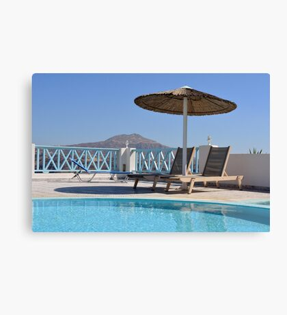 Two long chairs with straw umbrella by the swimming pool Canvas Print