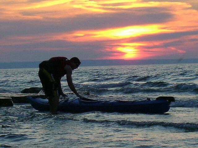 Kayaker on the beach by Robert Lake