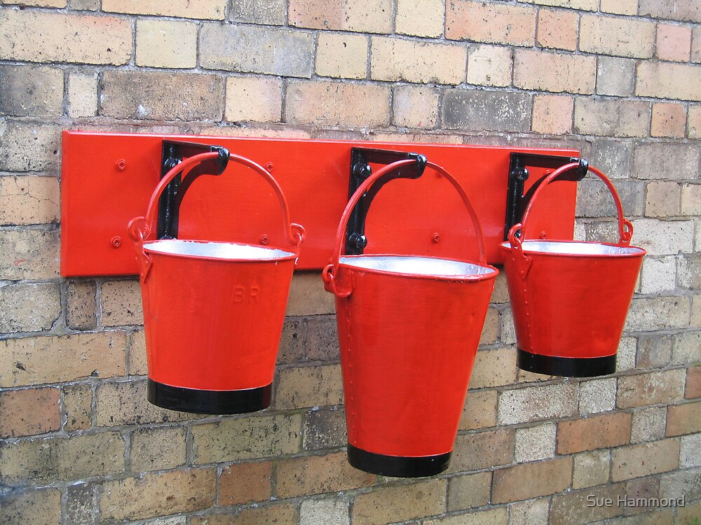Red buckets hanging on the wall by Sue Hammond
