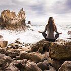 Meditating woman at beach by Bradley Hebdon