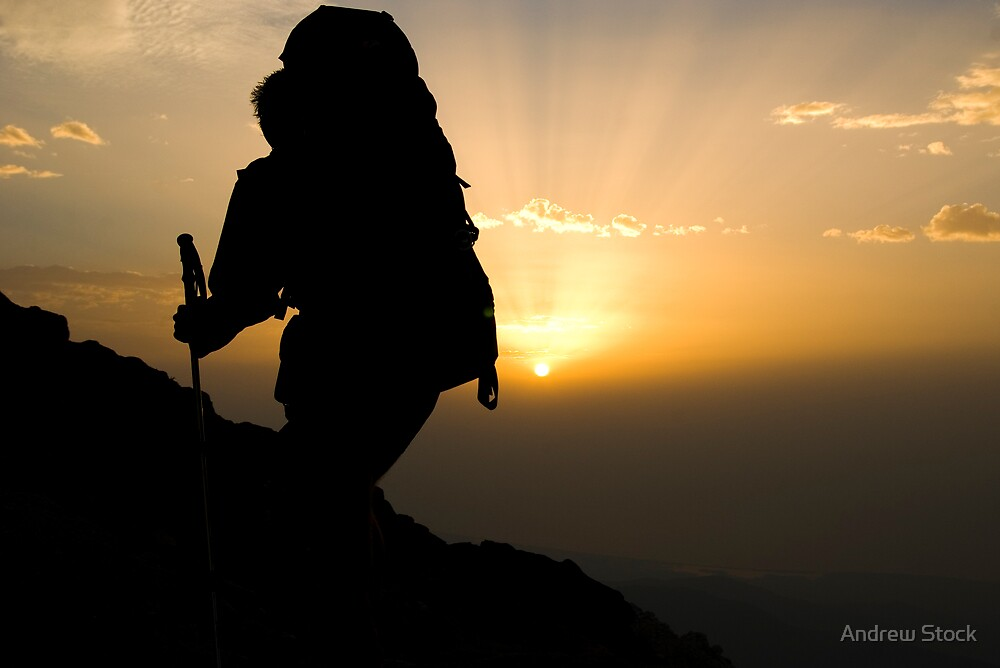 Silhouette of hiker against mountain sunrise by Andrew Stock