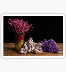 Three bundles of small  flowers on wood table top Sticker