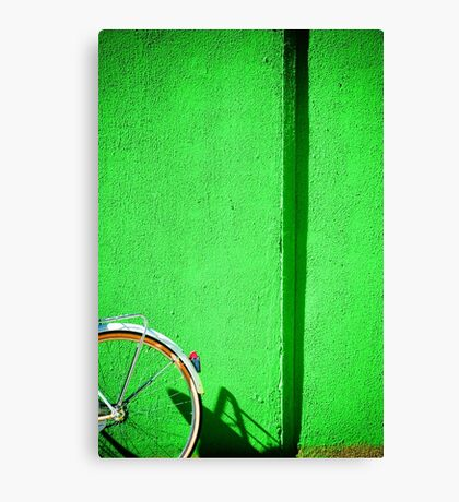 Bicycle wheel and green wall Canvas Print