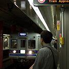 Train approaching, Tokyo, Japan by Norman Repacholi