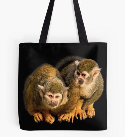 Two squirrel monkeys agains black background Tote Bag