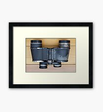 Old military binoculars on table Framed Print