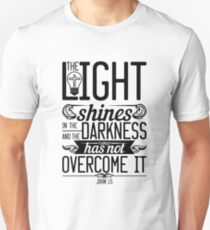 The light shines in the darkness, and the darkness has not overcomeit. Unisex T-Shirt