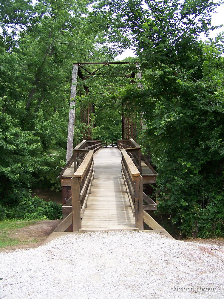 wooden bridge in woods by kimberly brown