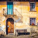 Old Italian facade with shadow and geraniums by Silvia Ganora