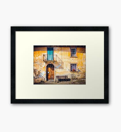Old Italian facade with shadow and geraniums Framed Print