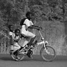 2 girls on the back a bicycle, coming from school, in Ghana, West Africa by Remo Kurka