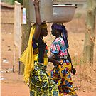African women fetching and carrying large bowls of water by Remo Kurka