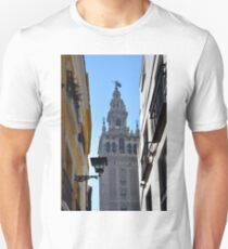 Buildings facades on narrow street with tower in Sevilla, Spain T-Shirt