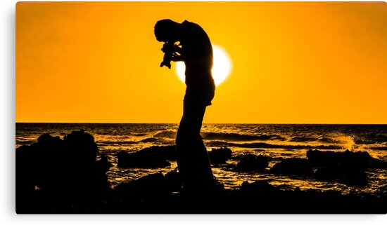 Silhouette of a photographer taking pictures on a beach at sunset by PhotoStock-Isra