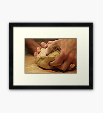 Hands of a baker kneading dough in a bakery at night. Framed Print