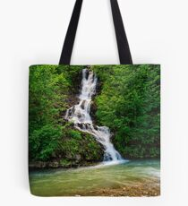 waterfall comes out of a hillside in forest Tote Bag