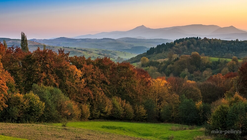 sunset over autumn forest in hazy mountains by mike-pellinni