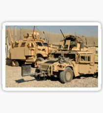 A M1114 humvee sits parked in front of a MaxxPro MRAP. Sticker