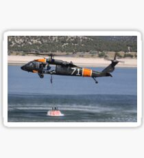 A U.S. Army UH-60 Black Hawk helicopter collects water from a reservoir. Sticker