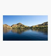 Coastline of mountains reflected  in blue ocean. Photographic Print